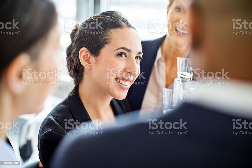 Happy businesswoman celebrating with colleagues in office stock photo
