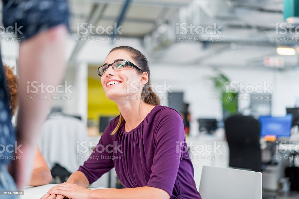 Happy businesswoman discussing with coworker stock photo