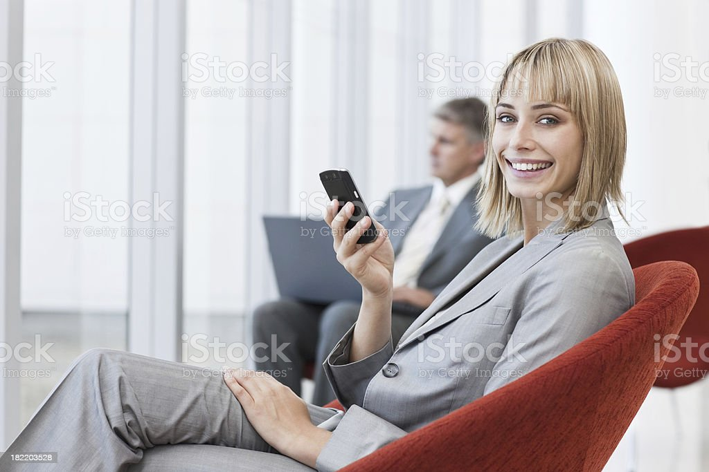 Happy businesswoman holding cellphone with colleagues in the background royalty-free stock photo