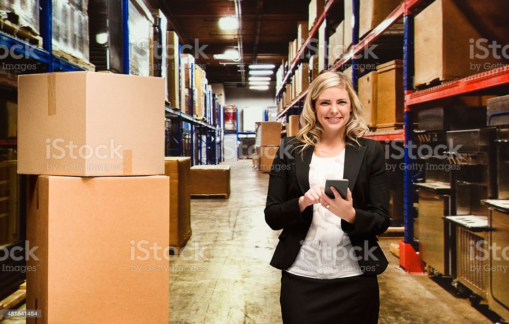 Happy businesswoman in warehouse and using mobile stock photo