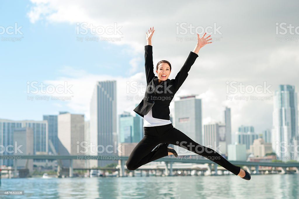 Happy Businesswoman Leaping with Miami Skyline stock photo
