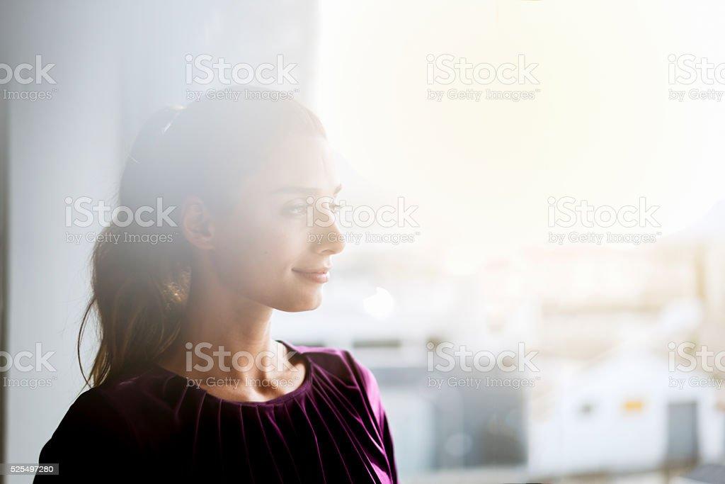 Happy businesswoman looking through window stock photo