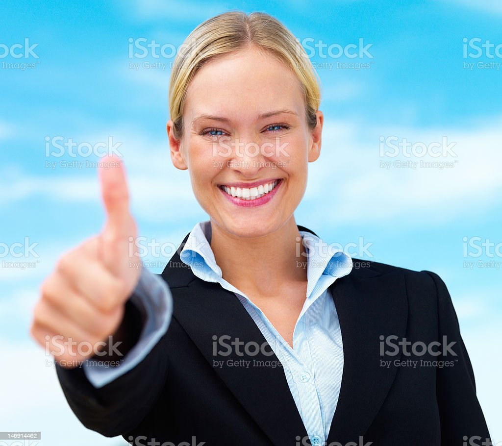 Happy businesswoman showing thumbs up sign royalty-free stock photo