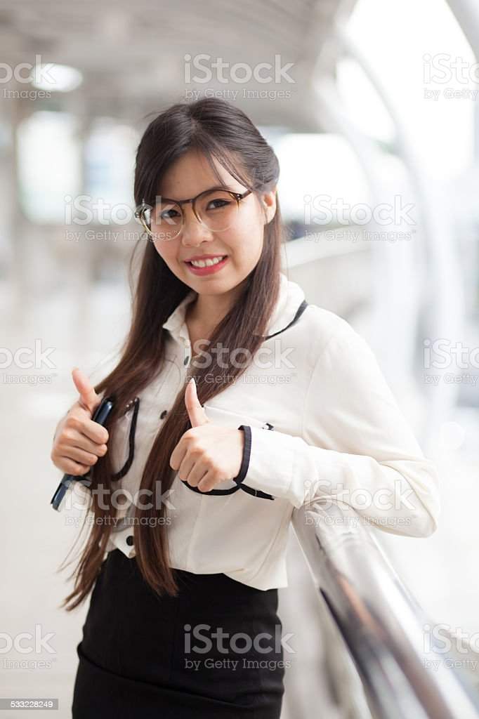 Happy businesswoman standing on sidewalk. stock photo