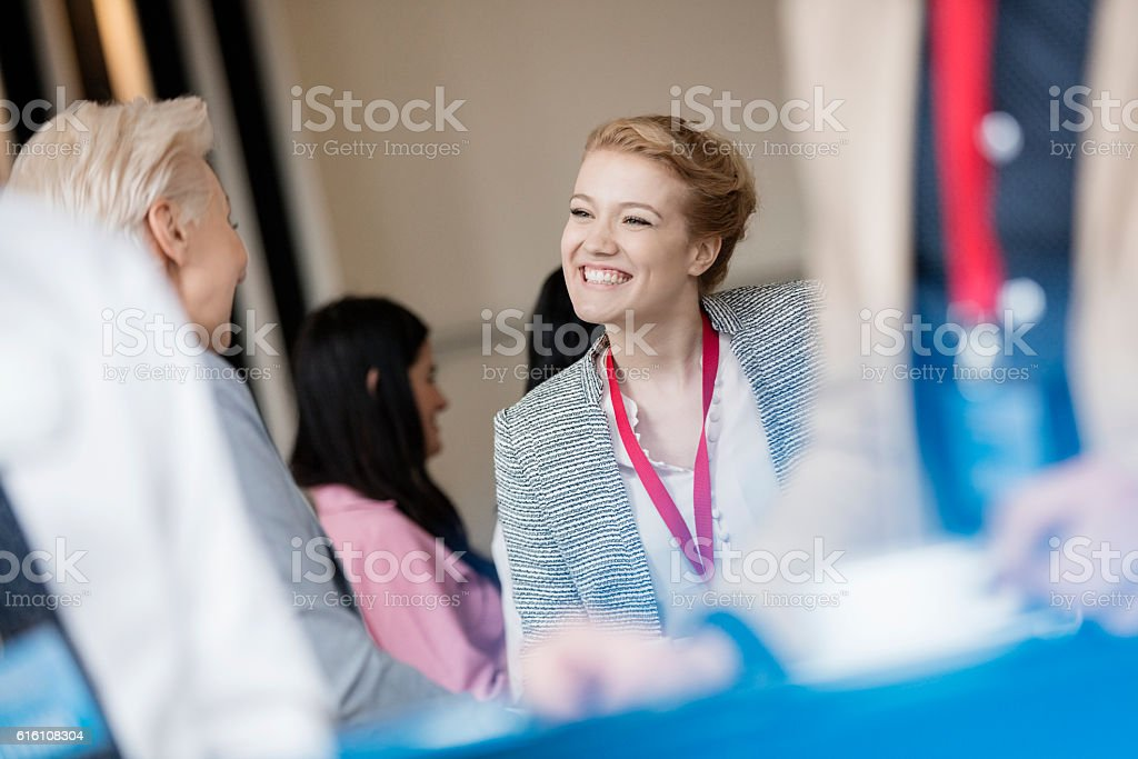 Happy businesswoman talking to colleague at lobby in convention center stock photo