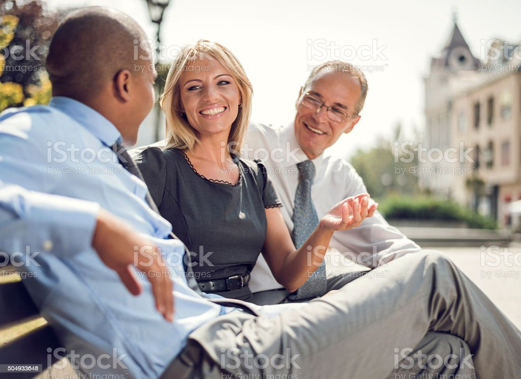 Happy businesswoman talking to her colleagues on a break. stock photo
