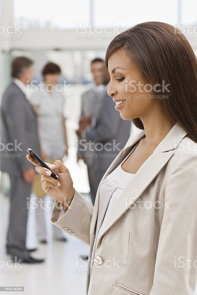 Happy businesswoman text messaging on mobile phone royalty-free stock photo