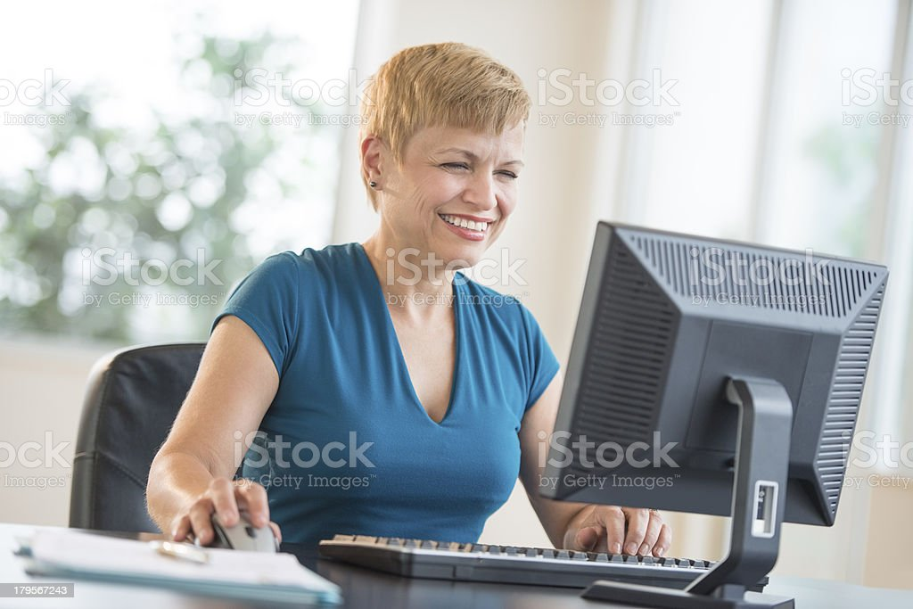 Happy Businesswoman Using Computer At Desk royalty-free stock photo
