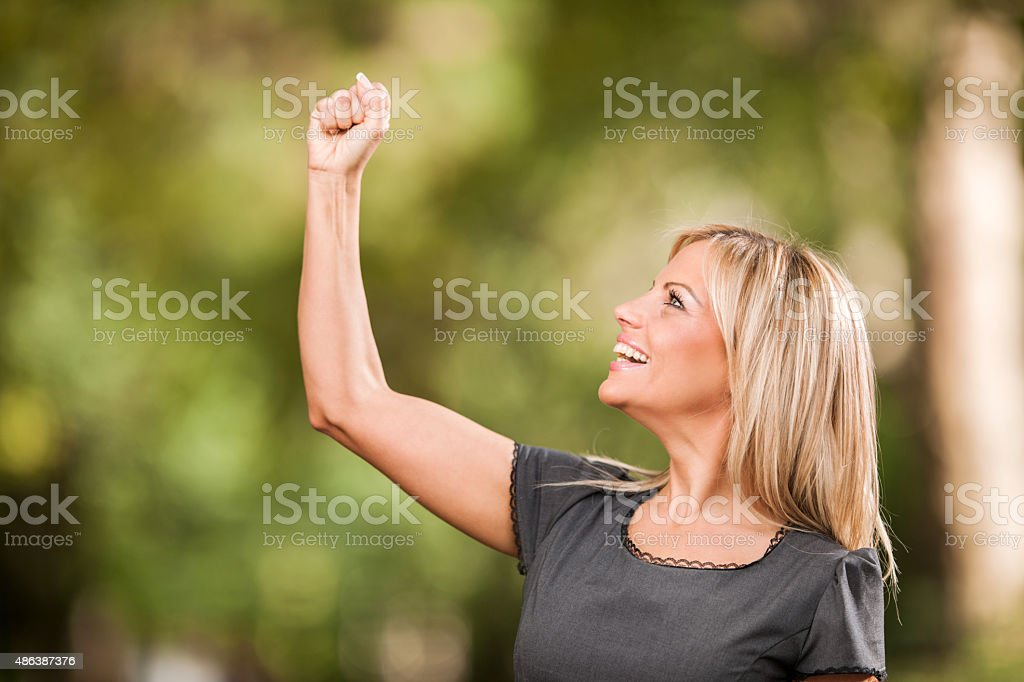 Happy businesswoman with clenched fist outdoors. stock photo