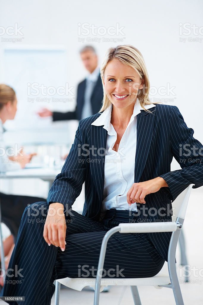 Happy businesswoman with colleagues discussing in the background royalty-free stock photo