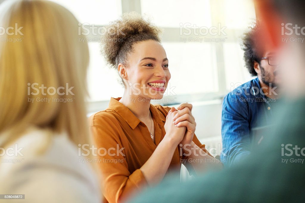 Happy businesswoman with colleagues in office stock photo