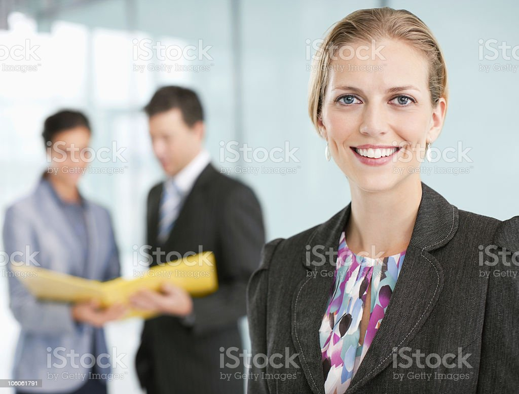 Happy businesswoman with her colleagues in the background royalty-free stock photo