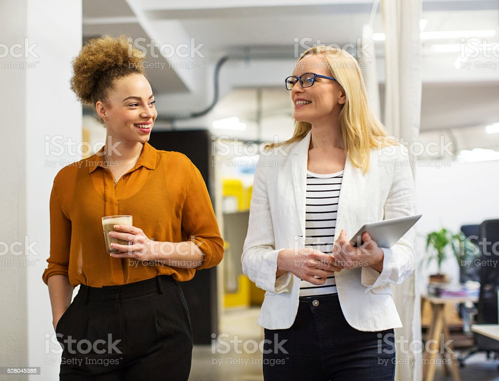 Happy businesswomen communicating in office stock photo