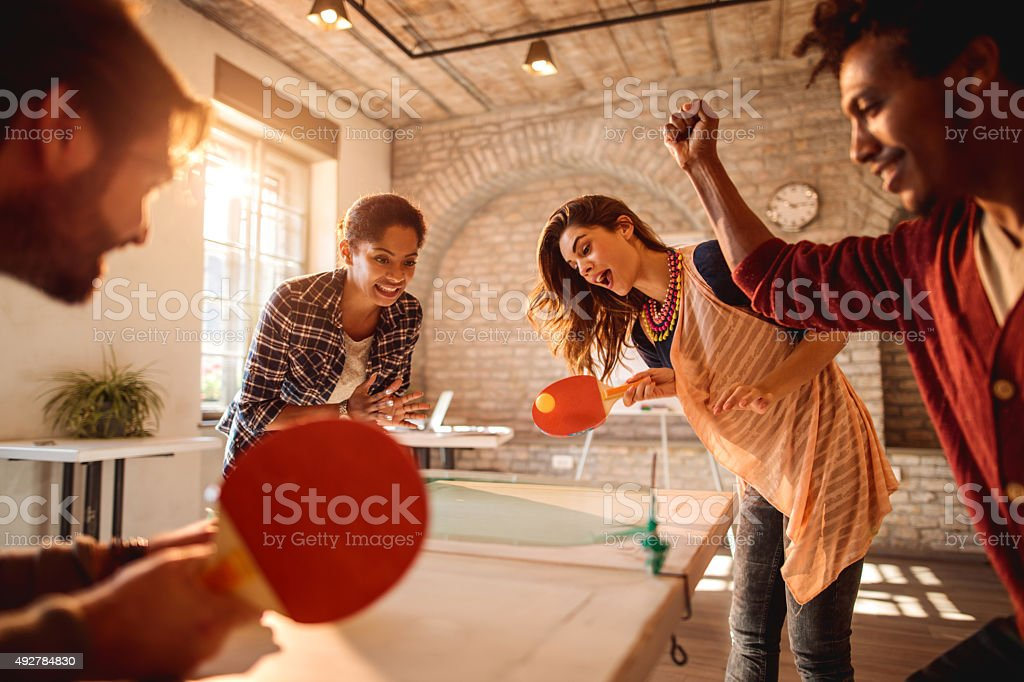 Happy businesswomen playing table tennis against businessmen at casual office. stock photo