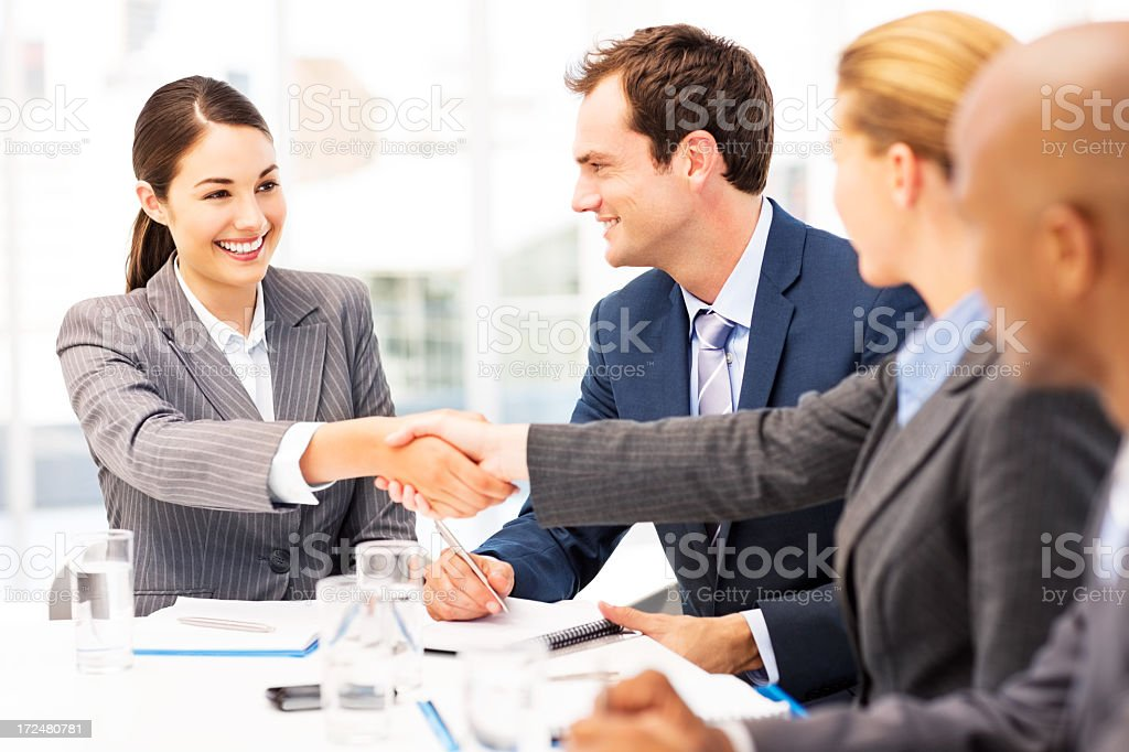 Happy Businesswomen Shaking Hands During Meeting stock photo