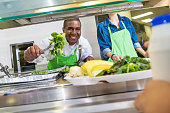 Happy cafeteria worker serving salad to student in lunch line