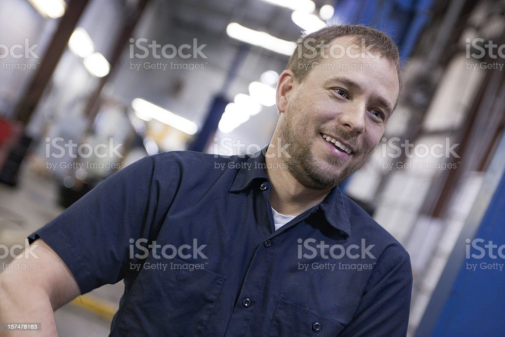 A happy car mechanic in a well lit garage royalty-free stock photo
