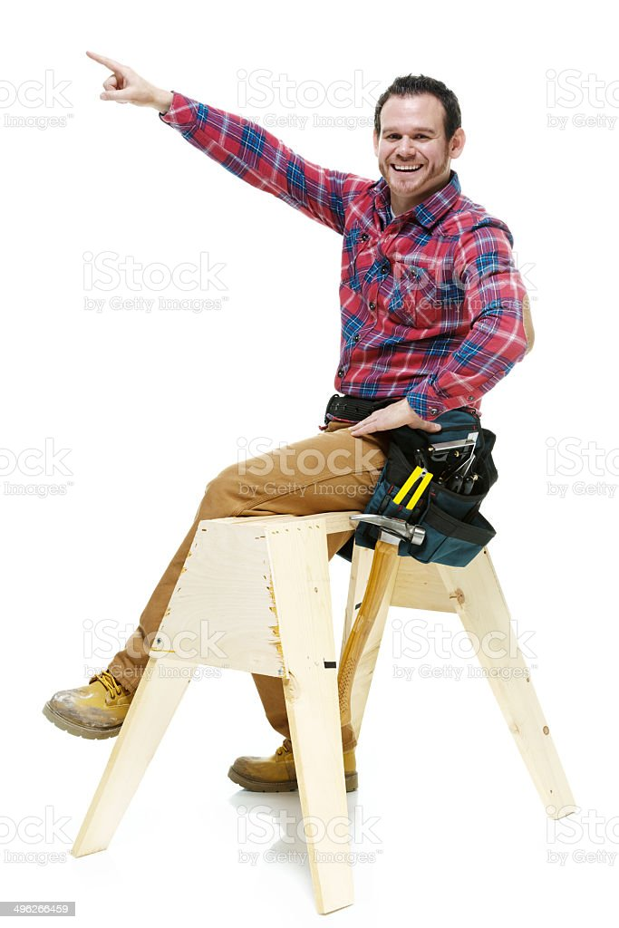 Happy carpenter sitting on sawhorse and pointing royalty-free stock photo