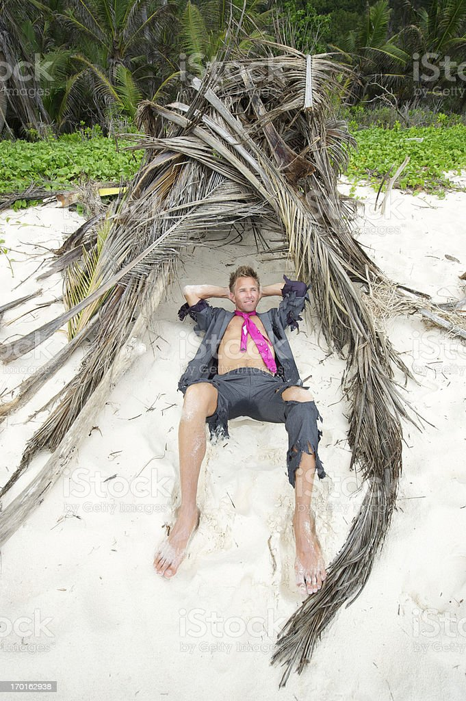 Happy Castaway Businessman Relaxes in Shelter stock photo