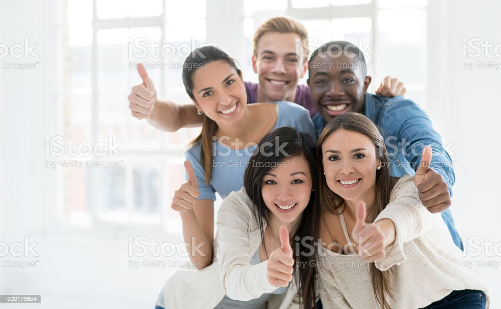 Happy casual group with thumbs up stock photo