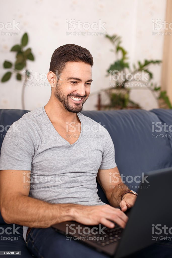 Happy casual man online communication on laptop stock photo