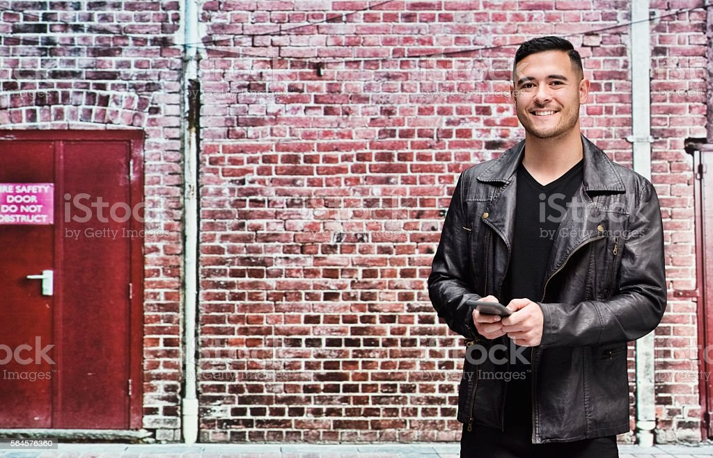 Happy casual man using phone in front of brick wall stock photo