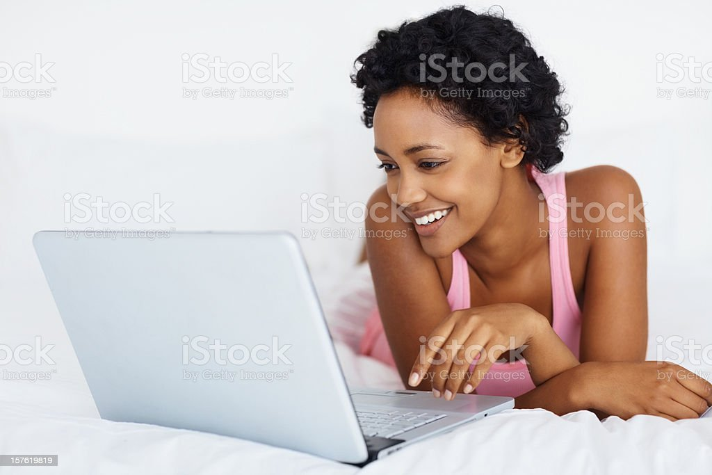 Happy casual woman using laptop while lying in bed royalty-free stock photo