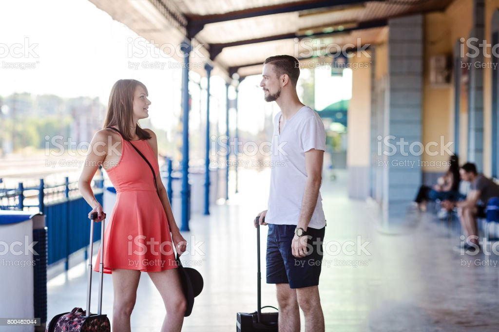 Happy caucasian couple standing with the suitcases at the train station, talking and looking at each other. Taken at summer daytime. stock photo