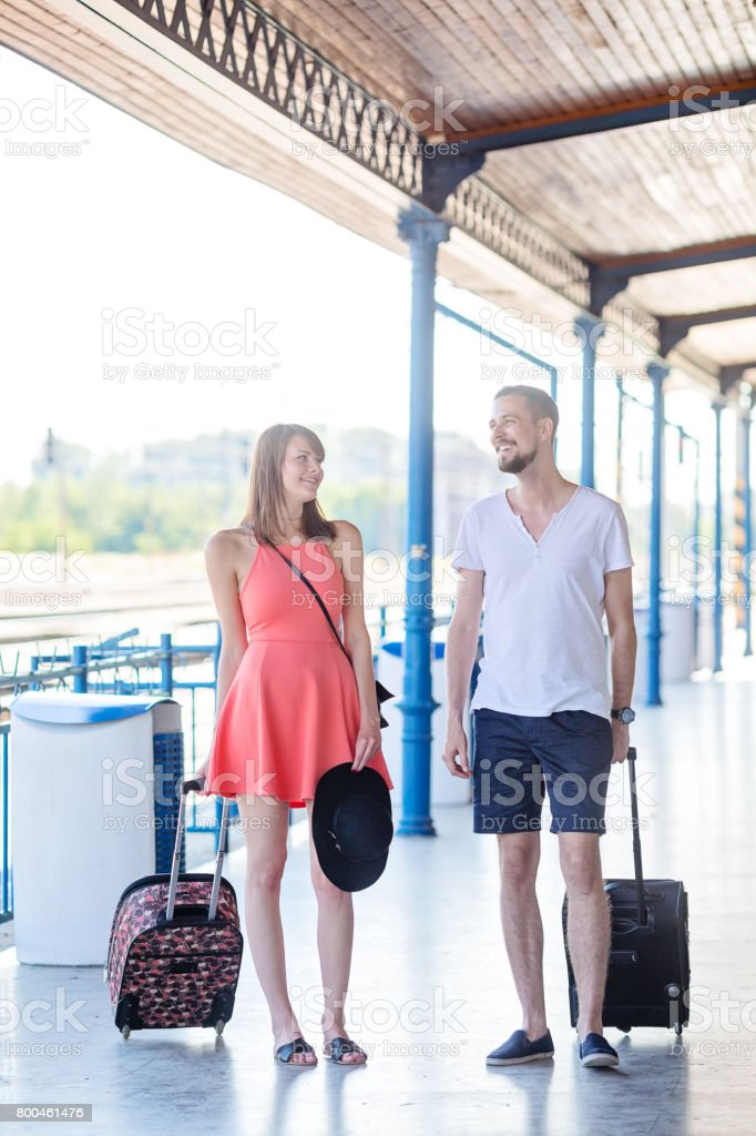 Happy caucasian couple wearing casual summer dress walking with the suitcases through the train station. Taken during sunny summer day. stock photo