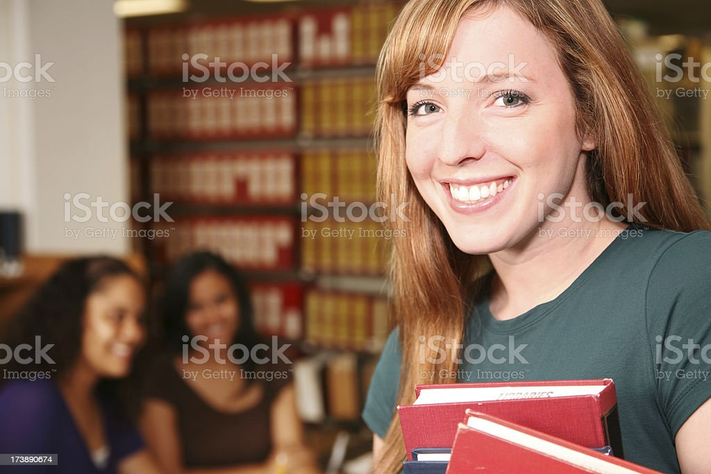 Happy Caucasian Female Student holding Books in the Library royalty-free stock photo
