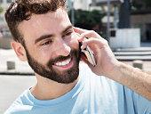 Happy caucasian man with beard at phone