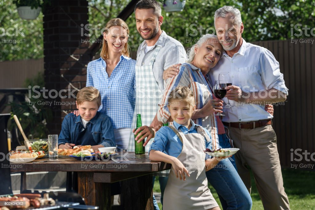 happy caucasian multi-generational family having picnic on patio at daytime stock photo
