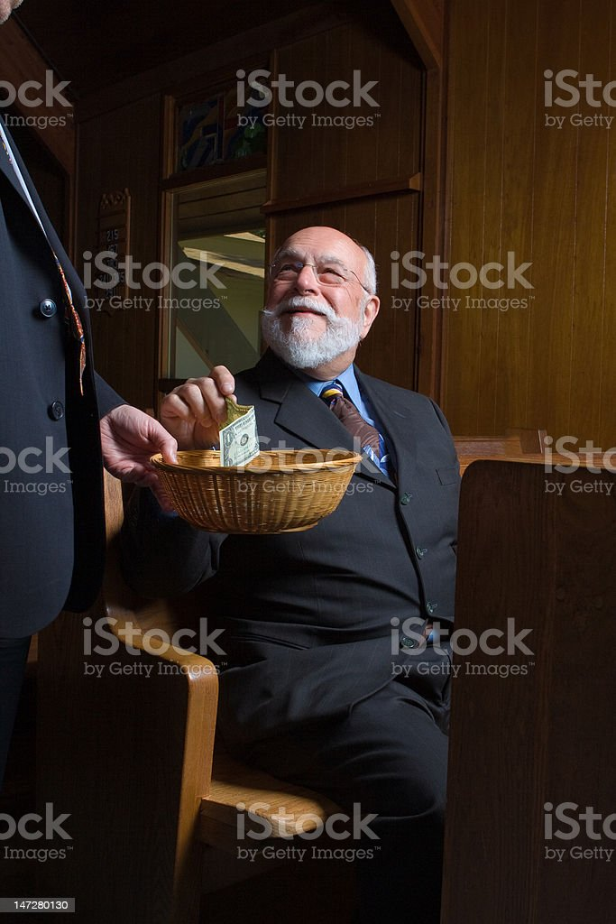 Happy Caucasian Senior Man Putting Money in Church Offering Basket stock photo