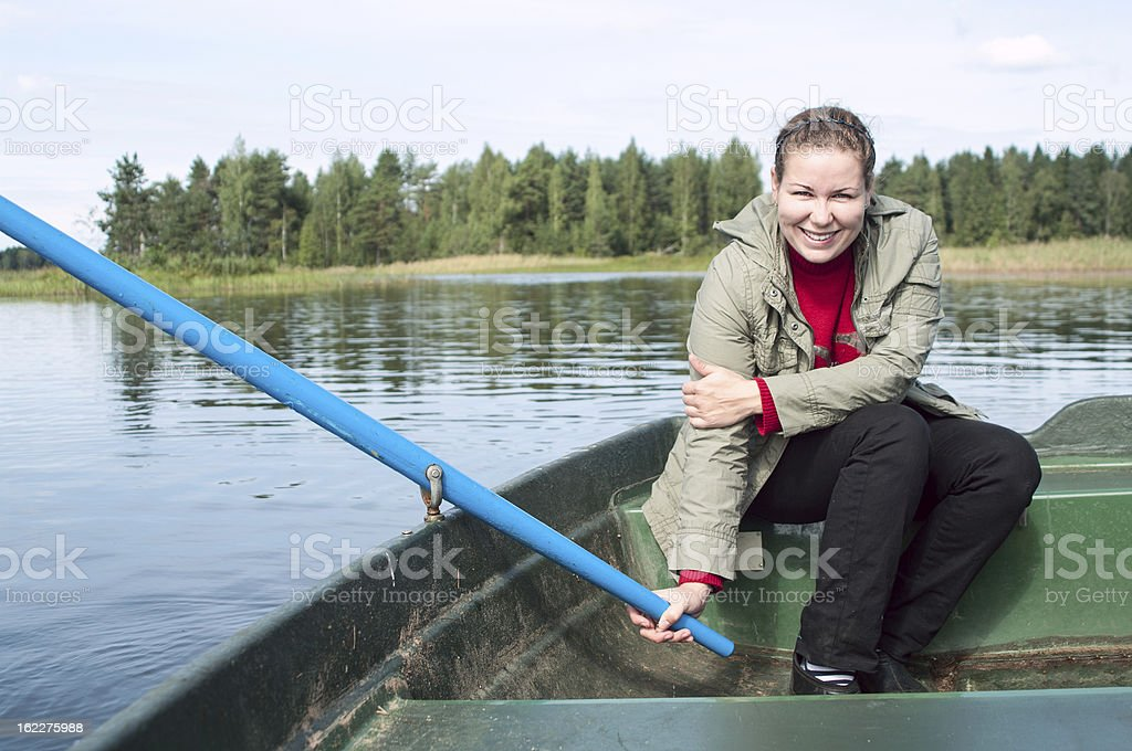 Happy Caucasian woman in row boat holding paddle royalty-free stock photo