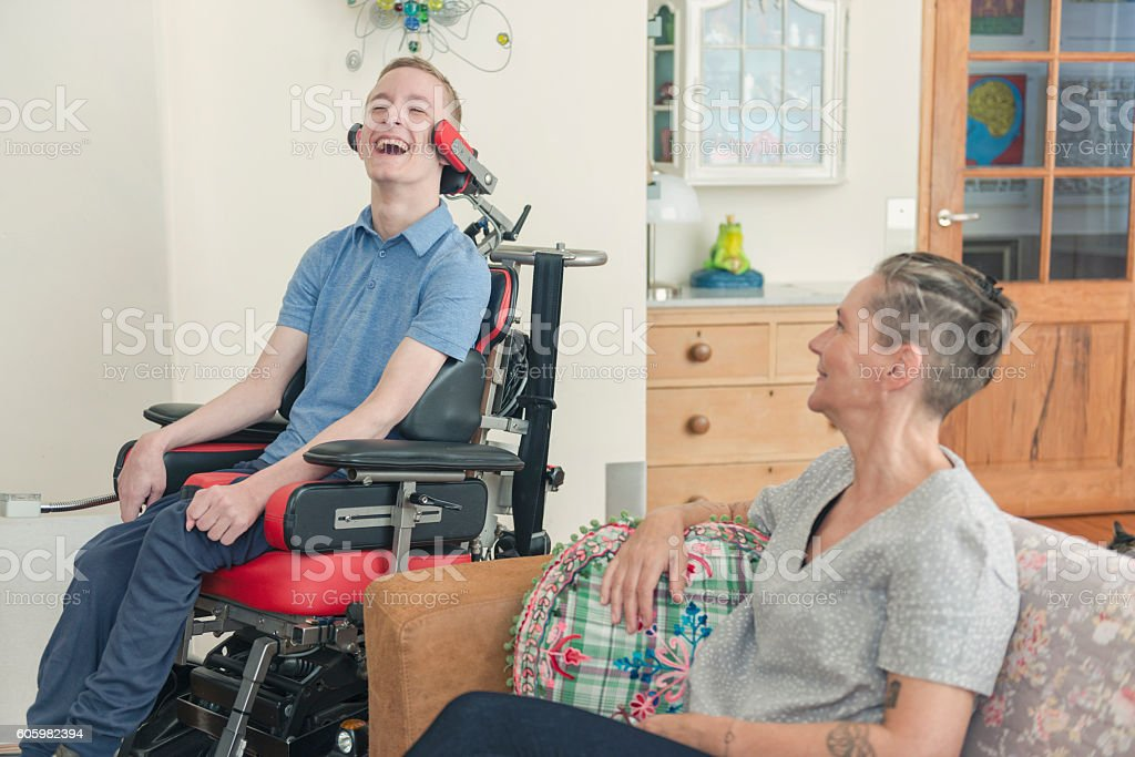 Happy cerebral palsy patient with his mom stock photo