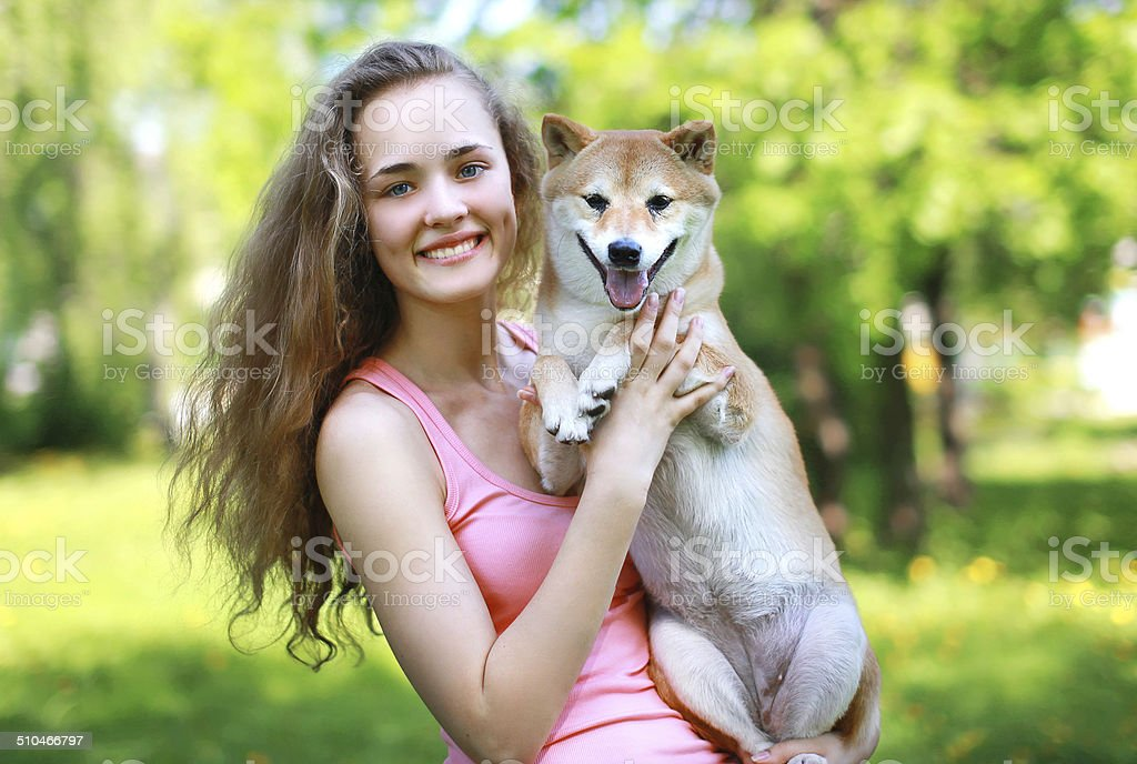 Happy charming girl owner holding loving dog stock photo
