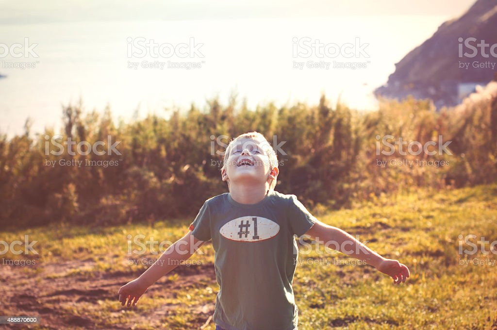 happy cheerful boy walking outdoors stock photo