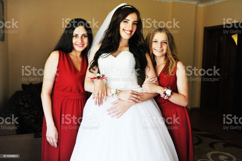 Happy cheerful brunette bride wearing at her room with two bridesmaids on red dress. stock photo