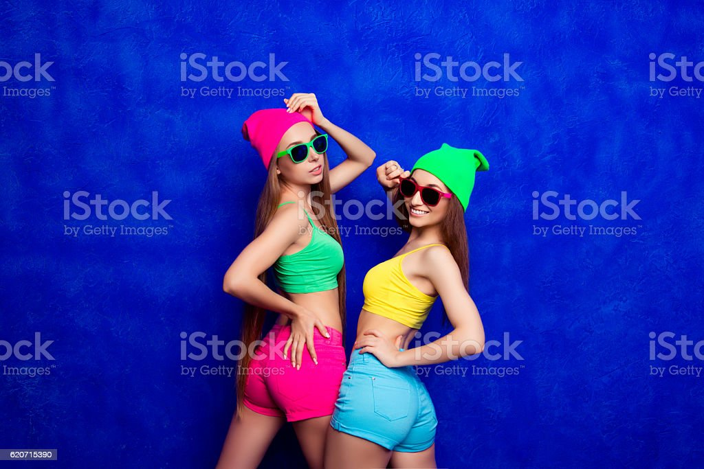 Happy cheerful hipster girls in glasses and color shorts stock photo