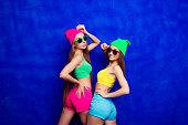 Happy cheerful hipster girls in glasses and color shorts