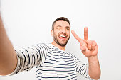Happy cheerful laughing man making selfie and showing two finger