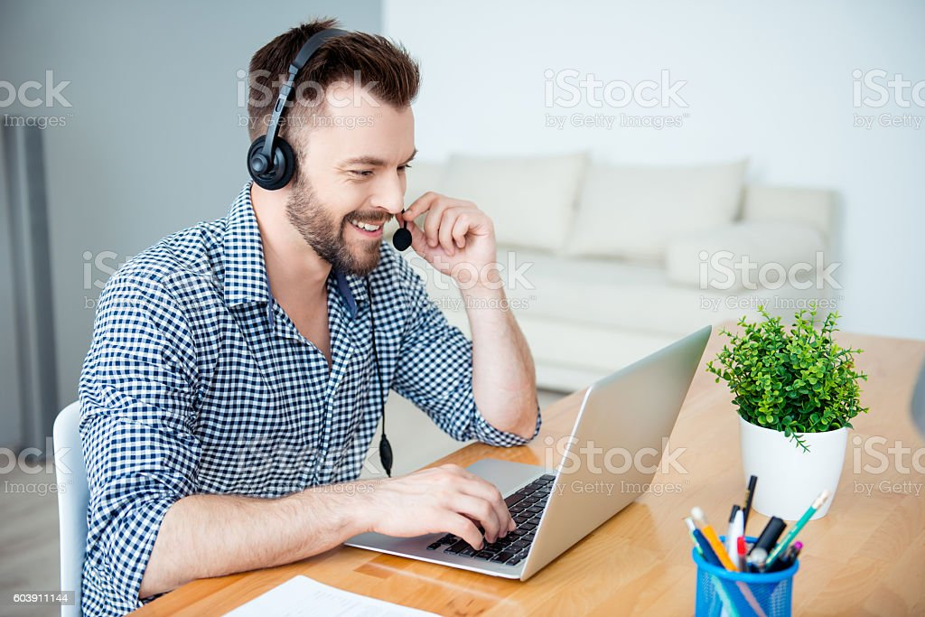 Happy cheerful young worker of call center in head-phones smiling stock photo