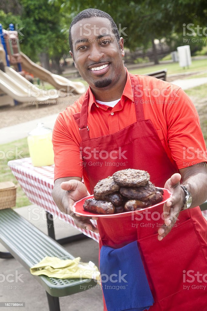 Happy Chef at Barbeque Holding Out Plate of Meat royalty-free stock photo