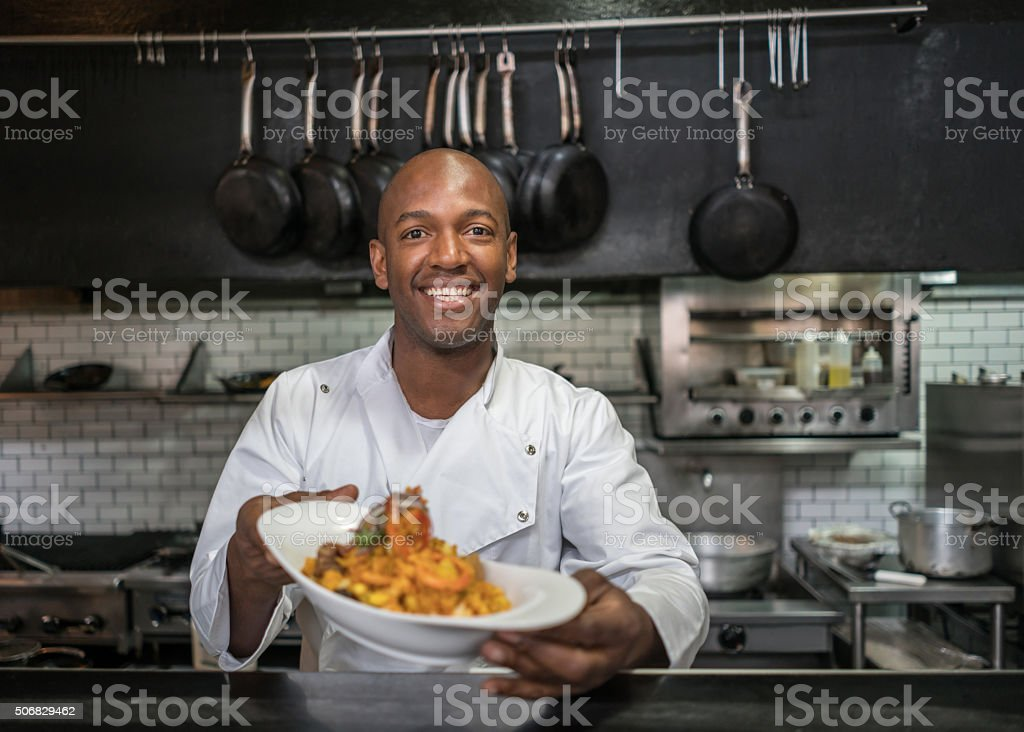 Happy chef presenting his plate stock photo