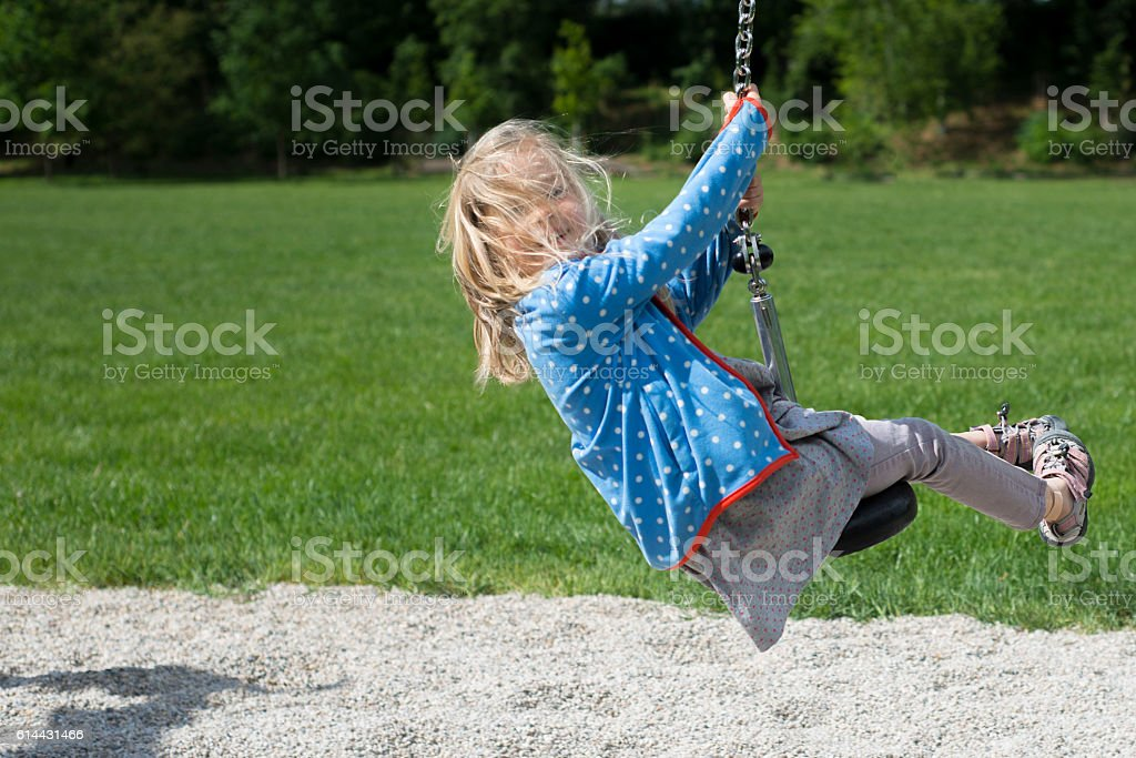 Happy Child blond girl  rids on Flying Fox play equipment stock photo