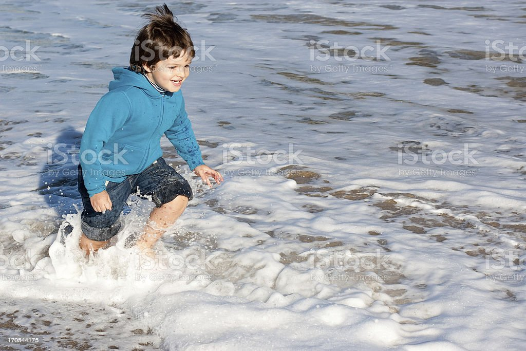Happy child caught by waves royalty-free stock photo