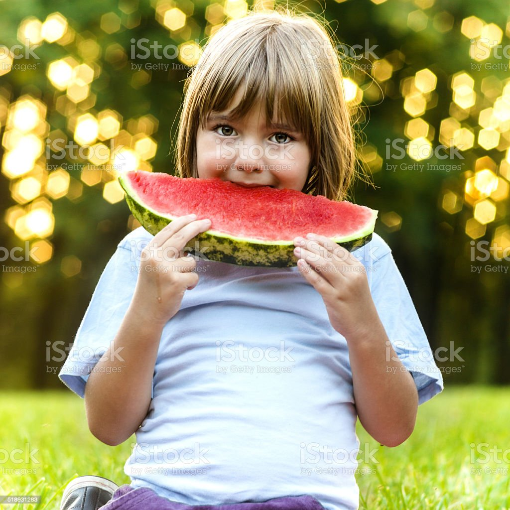 Happy child eating watermelon stock photo