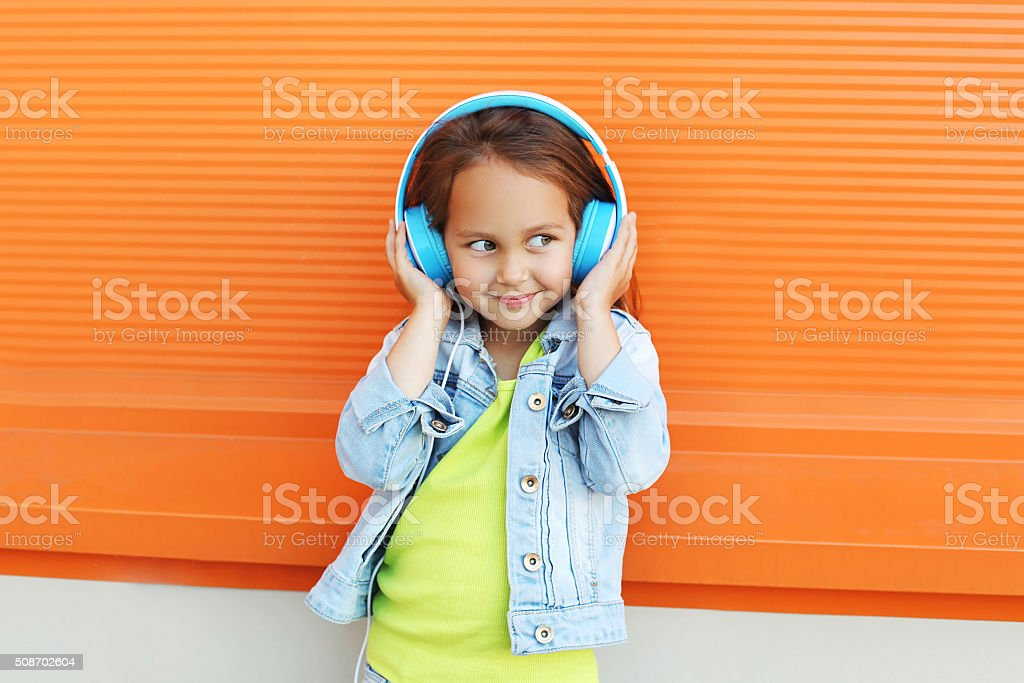 Happy child enjoys listens to music in headphones over orange stock photo