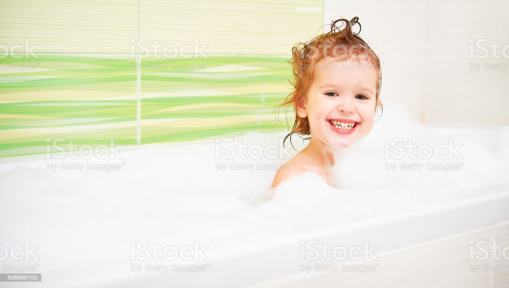 happy child girl bathes in  bath with foam and bubbles stock photo