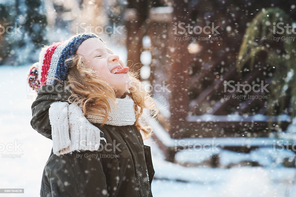 happy child girl catching snowflakes and playing on winter walk stock photo